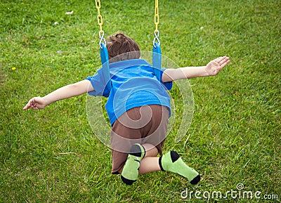Boy flying on a swing