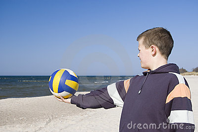 Boy with football on beach