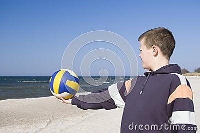 Boy with football on beach