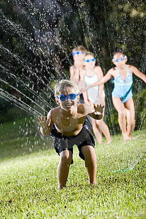 Boy with friends splashing in lawn sprinkler