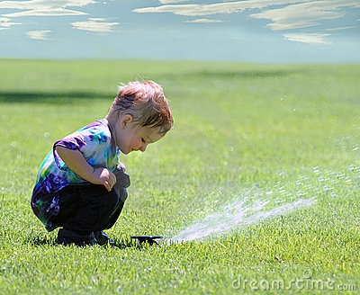 Boy and garden sprinkler