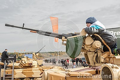 Boy gets acquainted with machine gun Editorial Stock Image