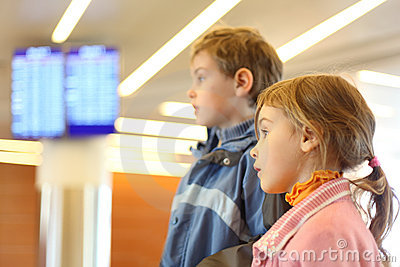 Boy and girl in airport screens on background