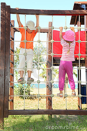 Boy and girl climbing on rope ladder at playground