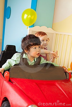 Boy and girl drive toy car