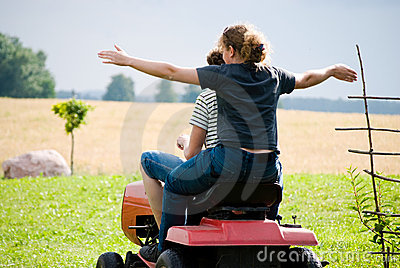 Boy and girl enjoy driving a tractor