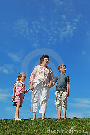 Boy and girl with grandmother standing on lawn