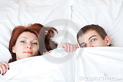 Boy and girl are hiding under the blanket