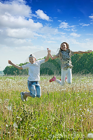Boy and girl jumping at meadow