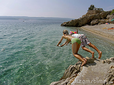 Boy and girl jumping into the sea from the rocks