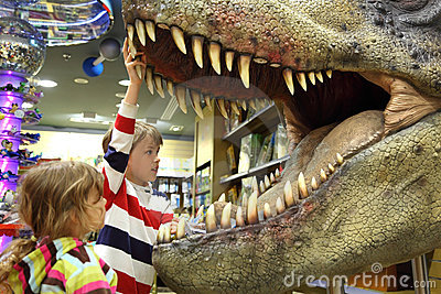 Boy and girl looking in tyrannosaurus opened mouth