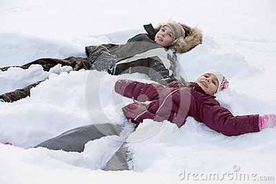 Boy and girl lying in the snow