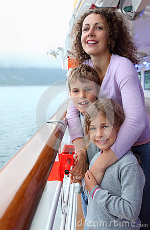 Boy and girl with mother stand on ship deck
