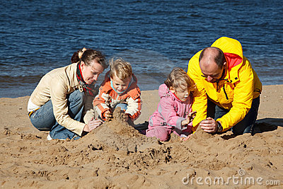 Boy and girl with parents play in sand on beach