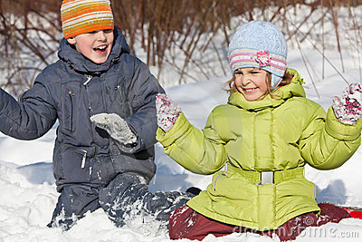 Boy and girl play sitting in snow in winter