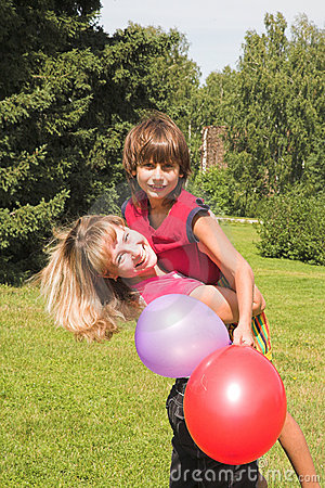 Boy and girl play in solar daytime