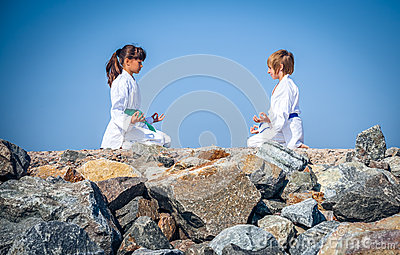 Boy and girl practising yoga on beach