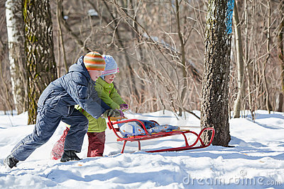 Boy and girl push sledge in winter in wood