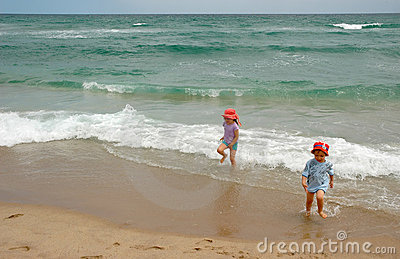 Boy and girl running from ocean surf