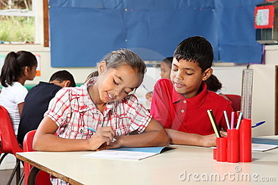 Boy and girl during school lesson in classroom