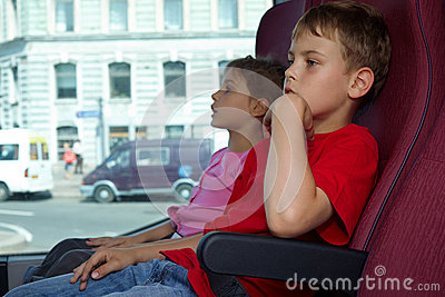 Boy and girl sit in chairs in bus