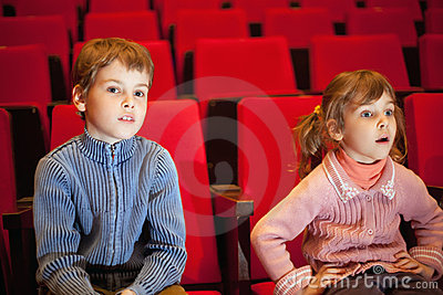 Boy and girl sitting on armchairs at cinema