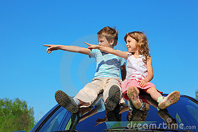 Boy and girl sitting on car roof