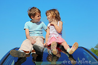 Boy and girl sitting on car roof on sky