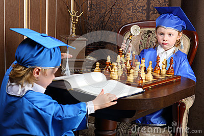 boy and girl sitting at the chess table Stock Photo