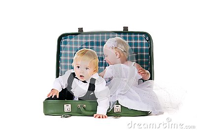 Boy and a girl sitting in a suitcase