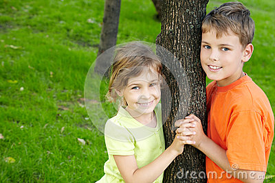Boy and girl stand on each side of tree