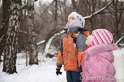 Boy and girl stand and look in park