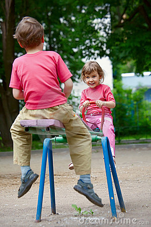 The boy and the girl on a swing in park