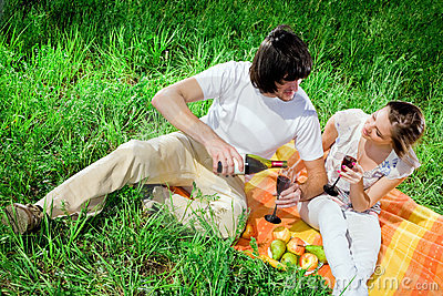 Boy and girl with wine on grass