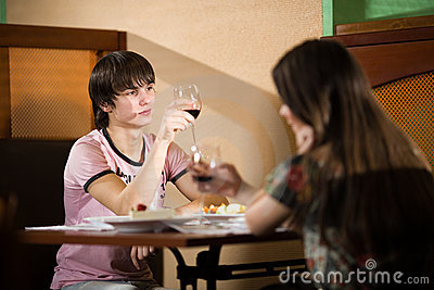 Boy and girl with wineglasses  at table