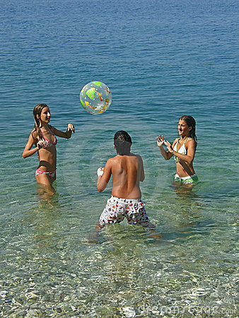 Boy and girls playing with ball on sea