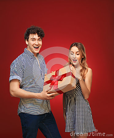 Free Boy Gives A Girl A Gift In A Pin Up Style, On A Red Bac Stock Images - 67663224