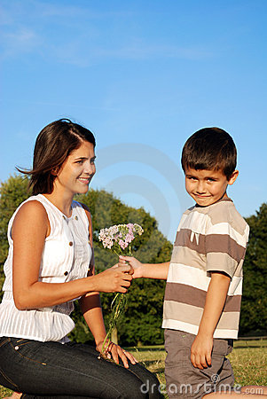 Boy giving flowers to mum