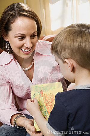 Boy giving mom a drawing.