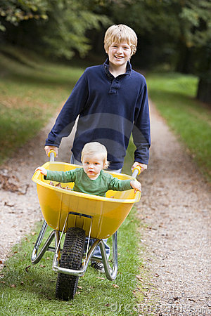 Boy giving toddler ride in wheelbarrow