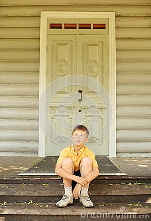 Boy in glasses seat on doorstep