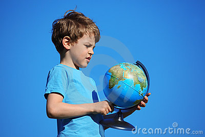Boy and globe against sky