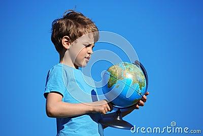 Boy and globe against sky