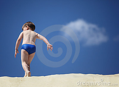 Boy going on sand,  rear view