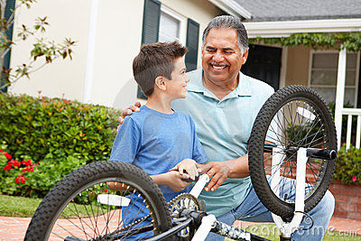 Boy and grandfather fixing bike together