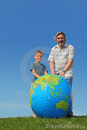 Boy and grandfather standing near globe Stock Photo