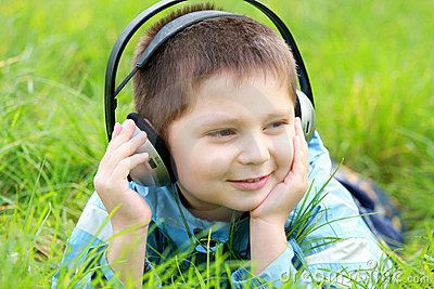 Boy in grass enjoying music