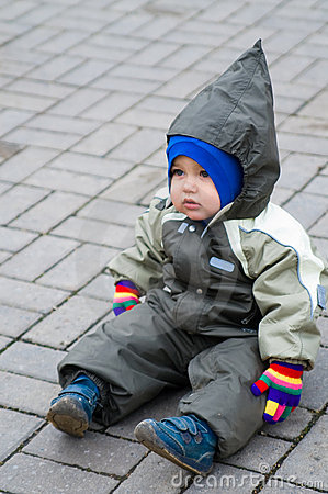A boy in green snowsuit sitting on paving stone