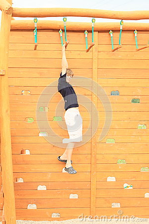 Boy hanging on obstacle course