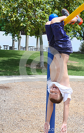 Free Boy Hanging Upside Down In Park Royalty Free Stock Photography - 25651097